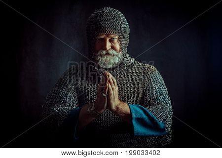 Portrait Of Praying Templar Knight On A Dark Background.