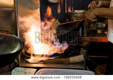 Asian Wok Cooking  With Flames In An Open Style Street Food Kitchen.