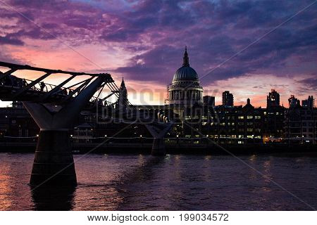 Sunset view of Saint Paul's Cathedral and Millennium Bridge on the River Thames in London