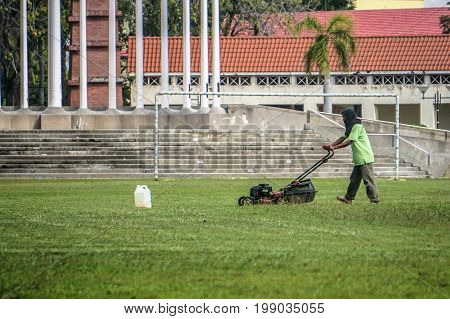 Labuan,Malaysia-July 14,2017:The worker of a garden cuts off a grass with grass cutter machine in Labuan,Malaysia on 14th July 2017