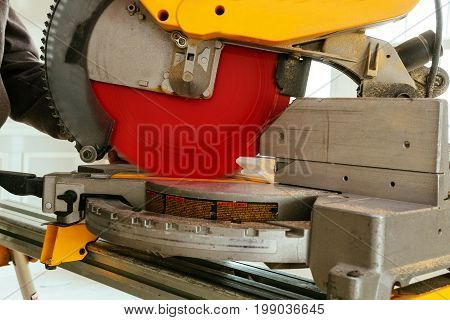 Closeupof Mature Sawing Lumber With Sliding Compound Miter Saw , Sawdust Flying Around