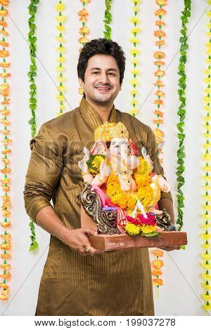 Indian handsome man in ethnic wear holding a Ganesh idol, welcoming God on Ganesh Chaturthi / festival at home with happy expressions