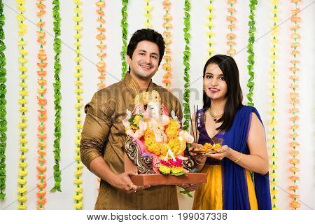 Ganesh Chaturthi - Smart Indian young couple in traditional wear or cloths while holding and welcoming Ganesh / ganpati idol / lord ganesha with pooja thali, standing over decorated garland background