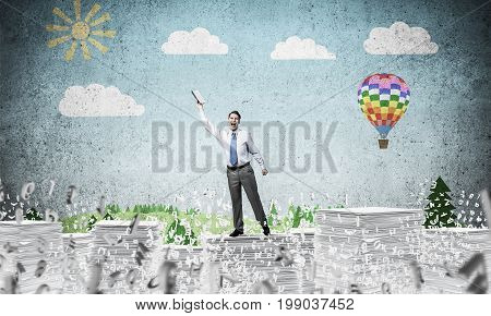 Businessman keeping hand with book up while standing among flying letters with drawn landscape on background. Mixed media.