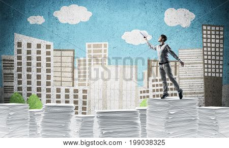 Man in casual wear keeping hand with book up while standing on pile of paper documents with drawn cityscape on background. Mixed media.