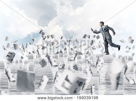 Businessman in black suit running with phone in hand among flying papers with cloudly skyscape on background. Mixed media.