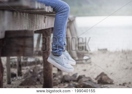 Woman's legs hanging on the old wooden bridge. Loneliness, isolation color scheme vintage style like no other.