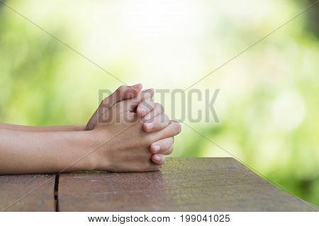 Hands on an old wooden table Natural background blurred bokeh pretty bright. Prayer to God