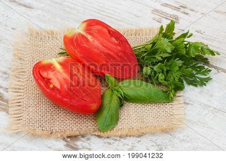 Red Tomato With Green Parsley And Basil On Jute Canvas