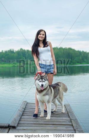 Young girl and her dog husky is sitting in a park near lake in summer