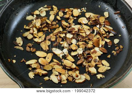 Roasting sliced almonds in olive oil in cast iron frying pan skillet