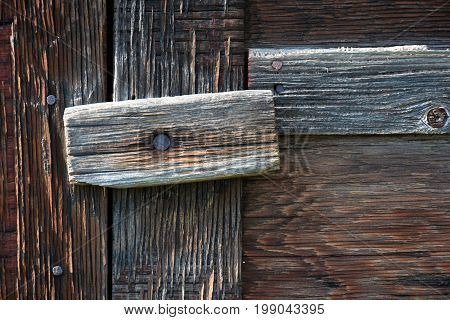 An abstract image of an old wooden latch on a barn door.