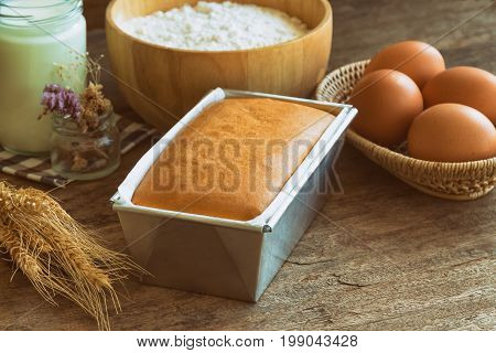 Bakery background with butter cake and ingredients:eggs milk flour and butter.Loaf of butter cake or pound cake on granite table. Homemade delicious pound cake in warm tone for background or wallpaper. Homemade bakery background concept.