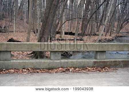 A concrete barrier prevents motorists from driving off of a bridge and falling into a creek in the Hammel Woods Forest Preserve in Shorewood, Illinois, during December.