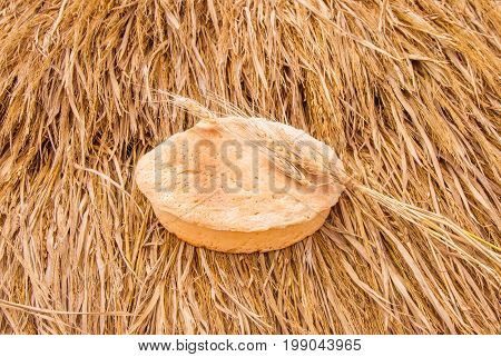 Freshly baked bread and wheat spikelets on haystack. Homemade traditional bakery product close-up. White whole grain loaves with wheat ears. Fresh loaf of bread. Selective focus.