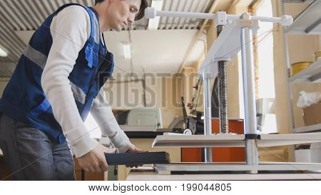 Worker in printing house is engaged in printing, polygraphic process
