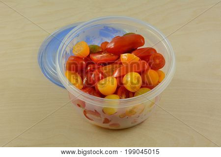 Food preparation done in advance of halved cherry tomatoes in plastic refrigerator storage container for quick meal time after work weekdays
