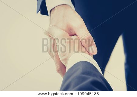 Handshake of businessmen in vintage (retro) color effect - success congratulation greeting & business partner concepts