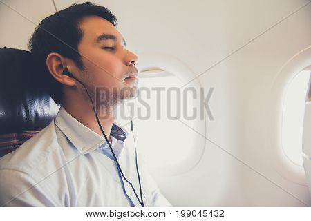 Sleeping male passenger wearing headsets listening to music on the airplane while traveling