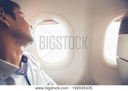 Tired passenger sleeping on the airplane at window seat