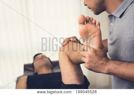 Therapist stretching athlete male patient in clinic - sport physical therapy concept