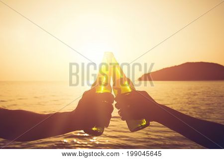 Couple hands holding beer bottles and clanging celebrating on holiday at the beach in summer sunset
