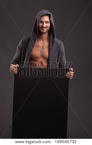 Young glad man portrait of a confident businessman showing presentation, pointing paper placard black background. Ideal for banners, registration forms, presentation, landings, presenting concept.