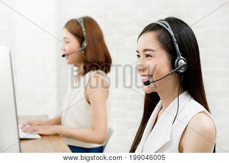 Smiling Asian woman telemarketing customer service agent team call center job concept