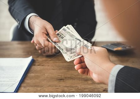 Businessman giving money Japanese yen currency to his partner at the table