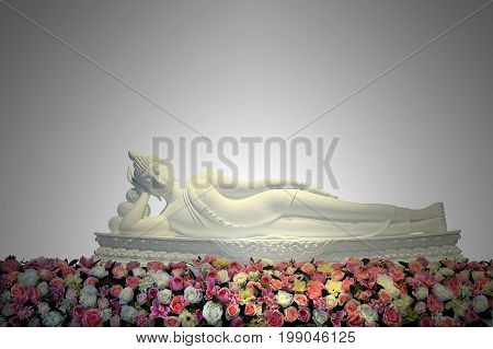 White reclining buddha statue with colorful flowers in main hall of Thai temple Wat Phasornkaew temple Phetchabun Thailand