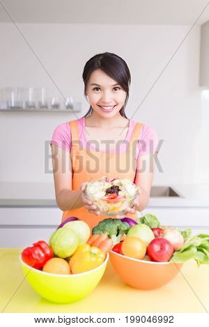 beauty housewife hold salad in the kitchen
