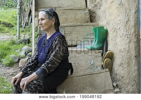 Gilan Province- IRAN-May 10 2017 Muslim woman seated on wooden steps and stare at outside of the frame in traditional cloth
