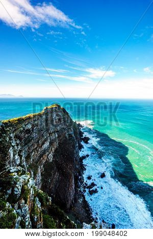 Rugged rocks and steep cliffs of Cape Point in the Cape of Good Hope Nature Reserve on the southern tip of the Cape Peninsula in South Africa surrounded by the turquoise waters of the Atlantic Ocean