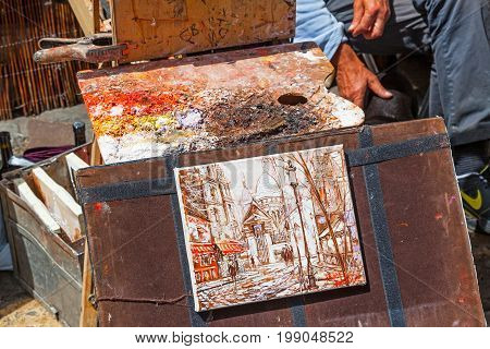 PARIS, FRANCE - JUNE 6, 2012: An artist's colorful palette and painting in shades of autumn in Montmartre in Paris.