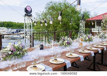 Glasses on the festive table setting. Wedding table decor concept. Table setting in classic style, setout. fine art. on the banks of the river