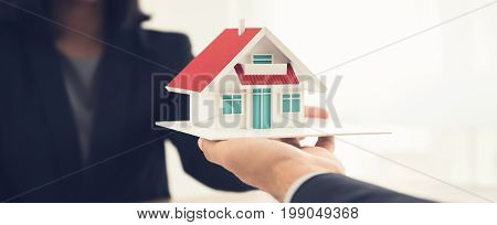 Real estate agent or architect presenting house model to client - panoramic banner