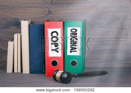 Original and Copy concept. Wooden gavel and books in background. Law and justice concept.