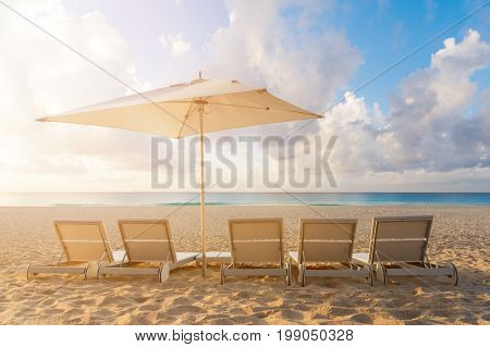 Five Beach chairs and Umbrella on the white sand beach with cloudy blue sky and sun.