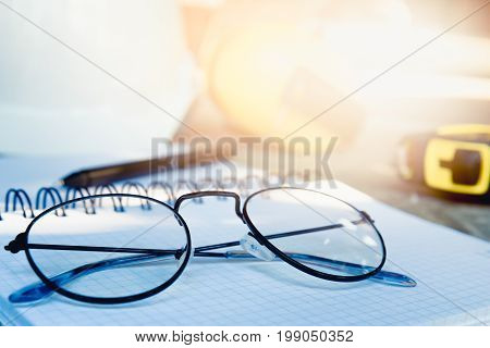 Engineers placed the spectacles on diary after work with sunlight. Go to relaxing in the weekend activity concept.