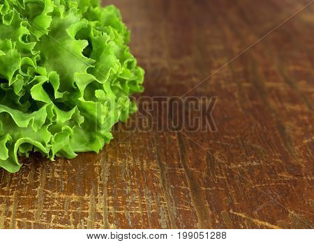 Green lettuce leaves. Lettuce leaves on wooden background.
