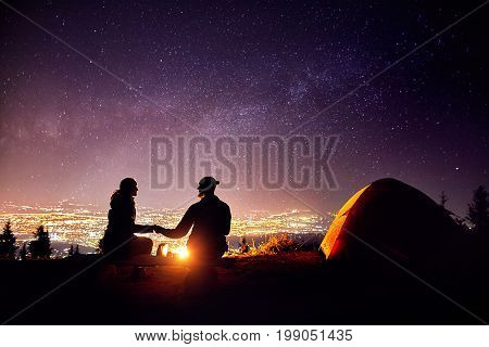 Romantic Couple Near Campfire At Starry Sky
