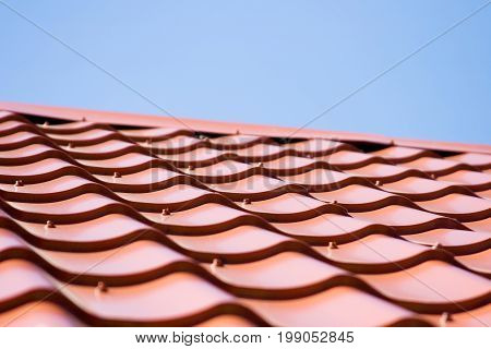 Red roof of metal roofing on the sky background