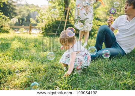 father and mother plays with his daughter with soapbubble outside in the park