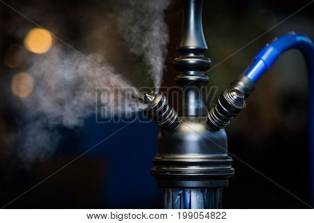 A hookah smokes on a blurred background