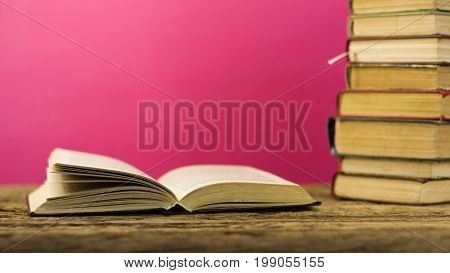 Books on an old wooden table. Beautiful pink background.