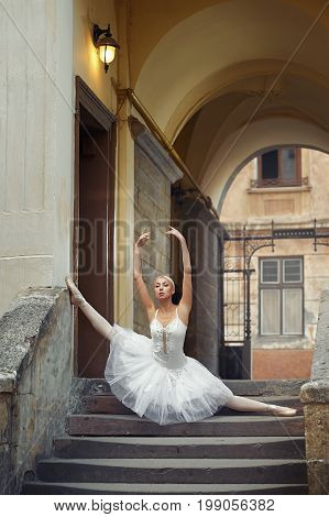 Shot of a beautiful ballerina performing outdoors dancing on the stairway of an old building doing splits grace elegance balance femininity beauty sensuality performance art.