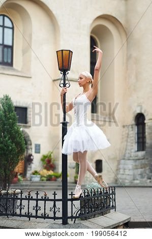 Graceful ballerina dancing outdoors on the city streets leaning on a street lamp gracefully.