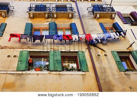 Clothes hanging on a clothesline outside the building window in Venice, Italy