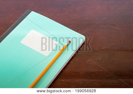 Closed notepad with white lable and pencil on a table