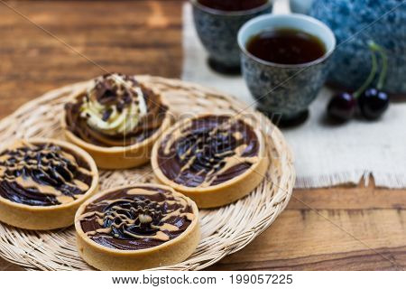 Chocolate mousse tarts basket cakes sweet tea on the wodden table
